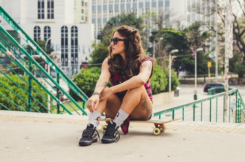 Photo of Woman Sitting on Skateboard While Looking Away