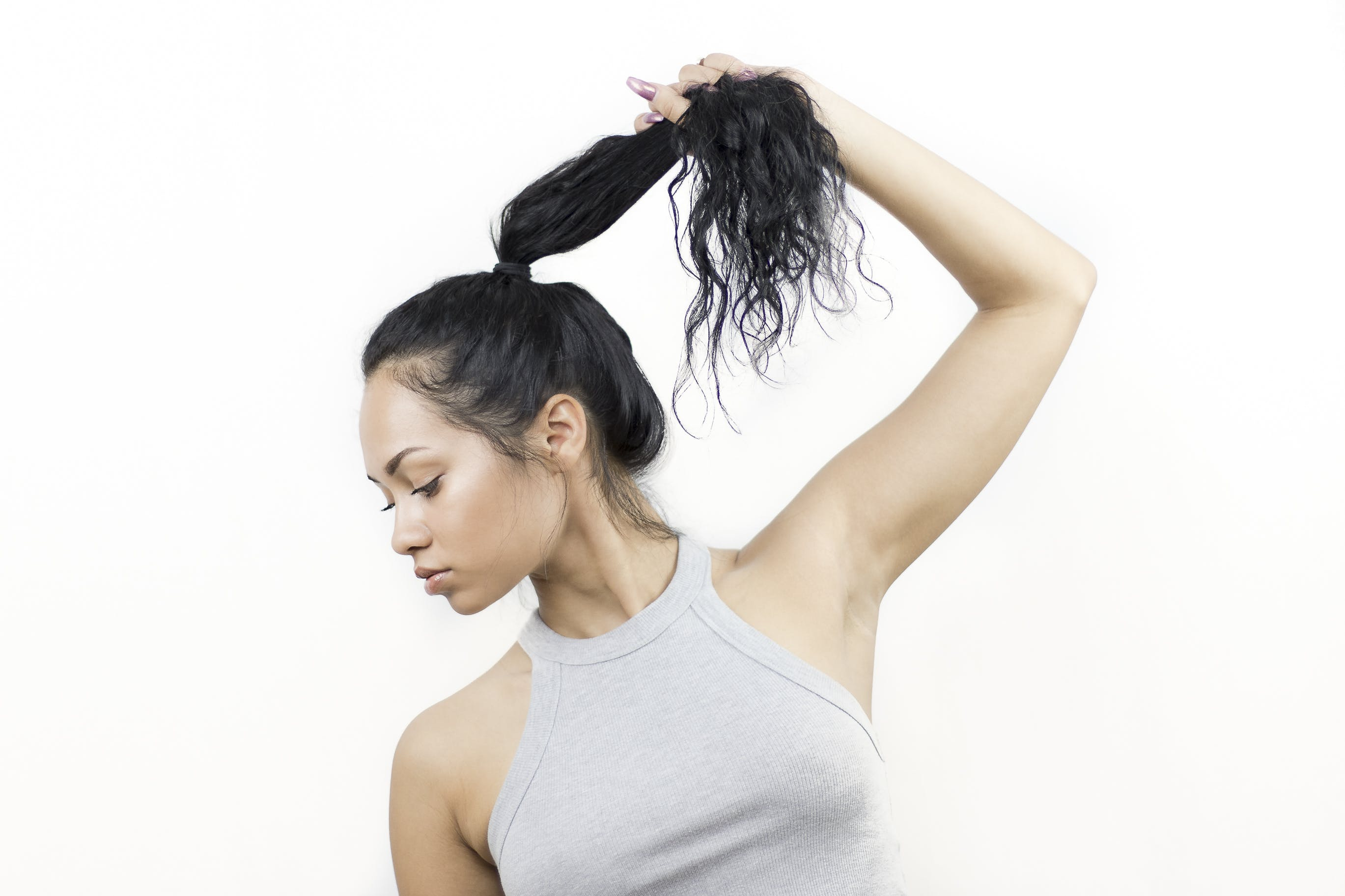Photo of Woman in Gray Sleeveless Top Holding Her Hair