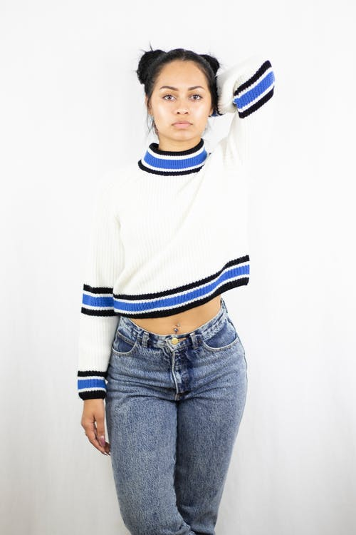 Photo of Woman in White and Blue Sweater and Blue Denim Jeans Posing In Front of White Background