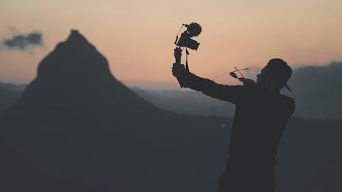Foto profissional grátis de alto, ao ar livre, boné, câmera