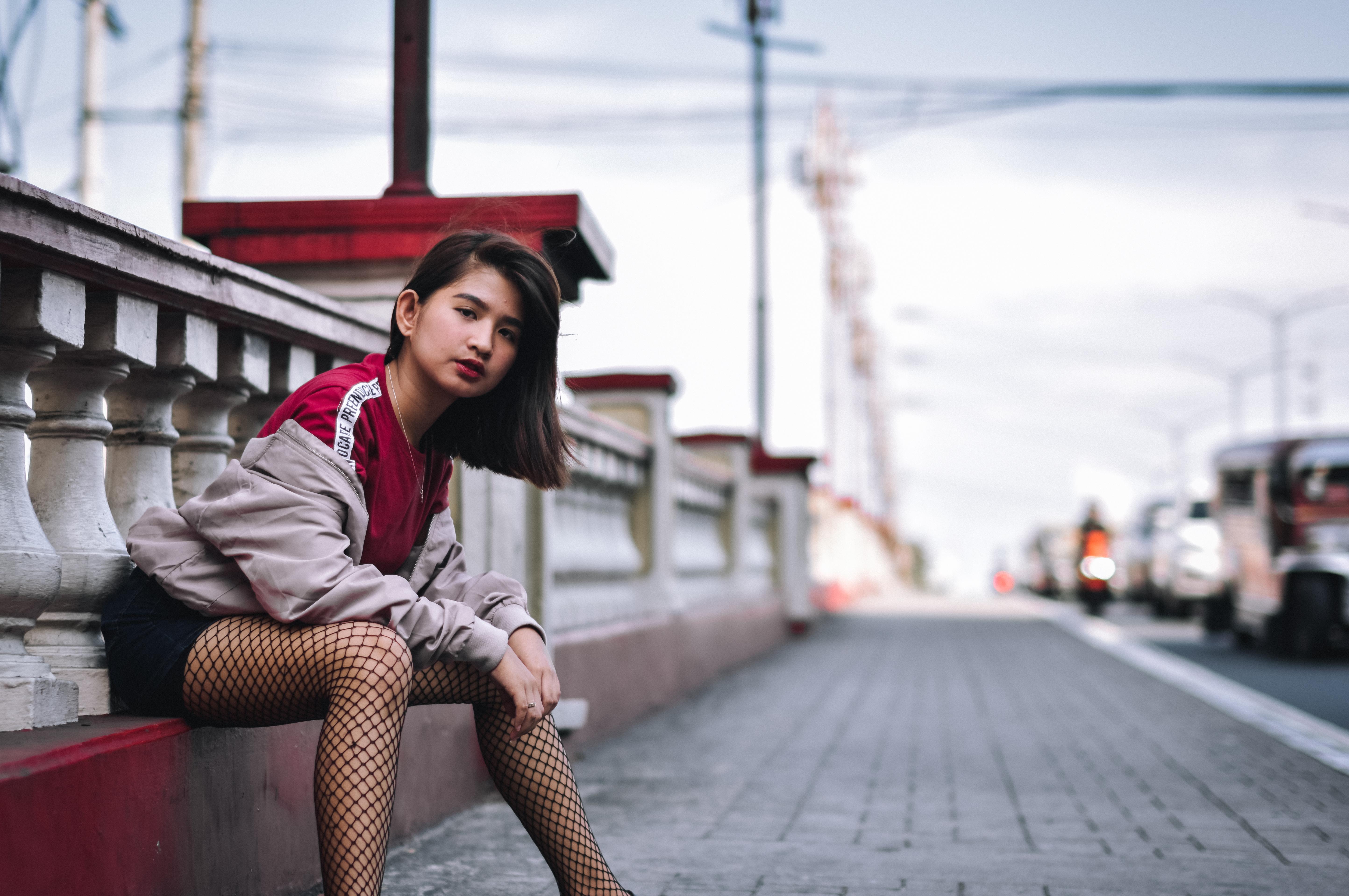 Woman Sitting on Concrete Pavement Near Road