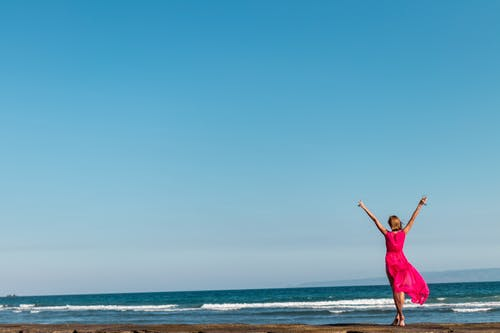 Woman Wearing Pink Dress Standing on Shore