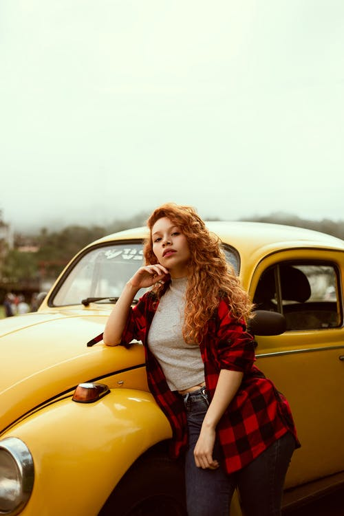 Woman in Red and Black Flannel Shirt Leaning on Yellow Volkswagen Beetle