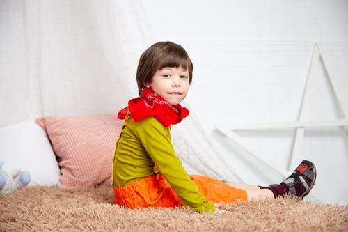 Boy Sitting On Brown Area Rug