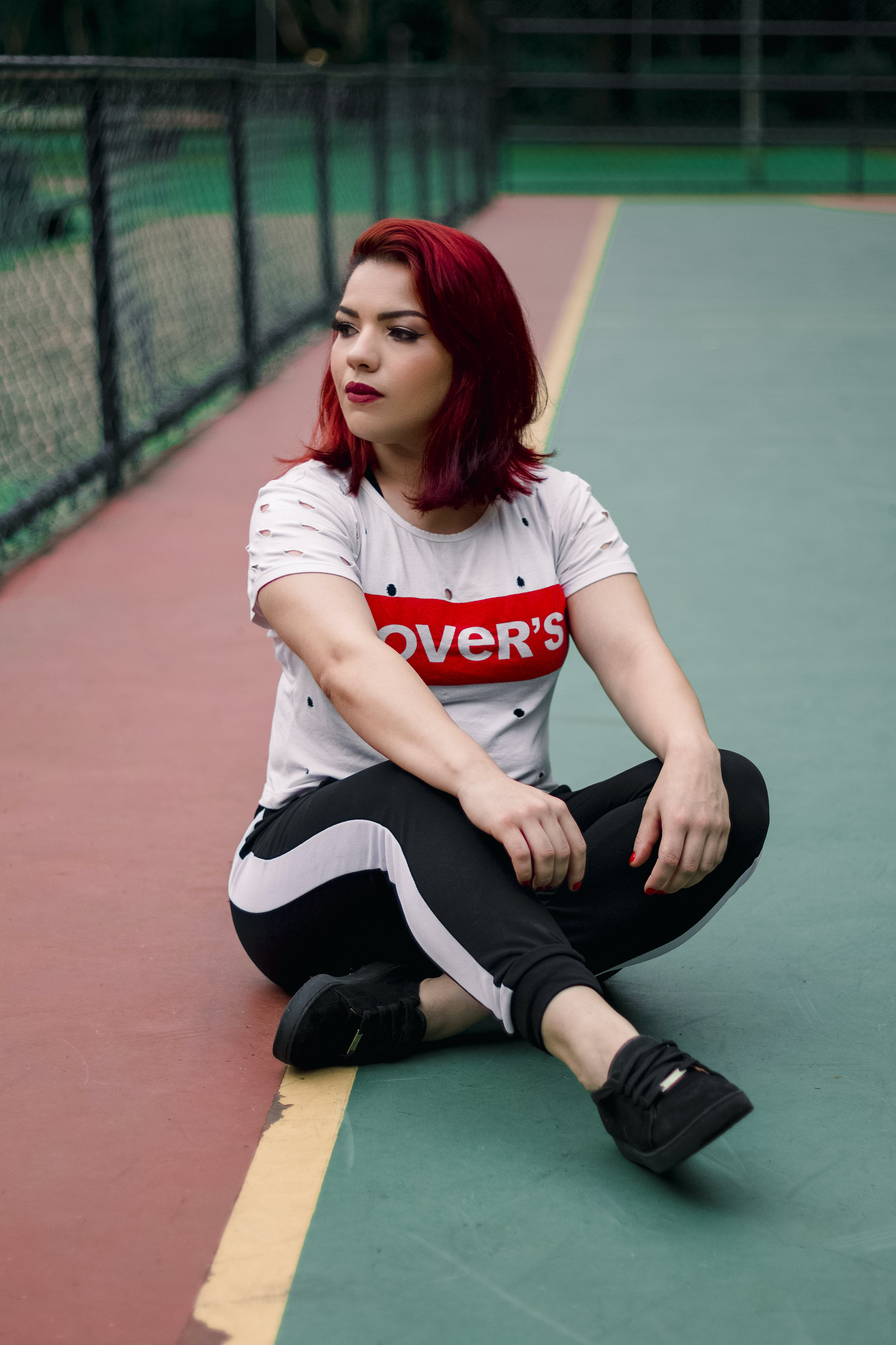 Woman Wearing Black And White Track Pants Sitting On Ground