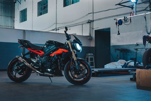Photo of Orange and Black Motorcycle Parked in Warehouse