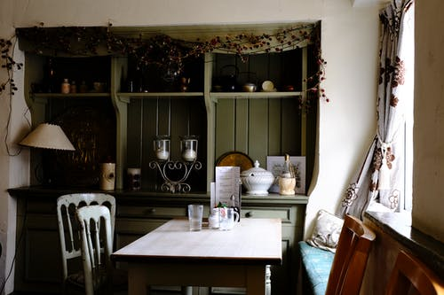 Green Display Cabinet and White Dining Set in a Kitchen