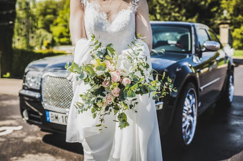 Woman in White Wedding Dress Carrying Bouquet in Front of Black Car