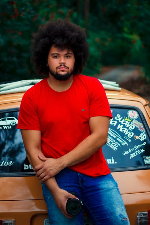 A man wearing a red t shirt leaning on a car