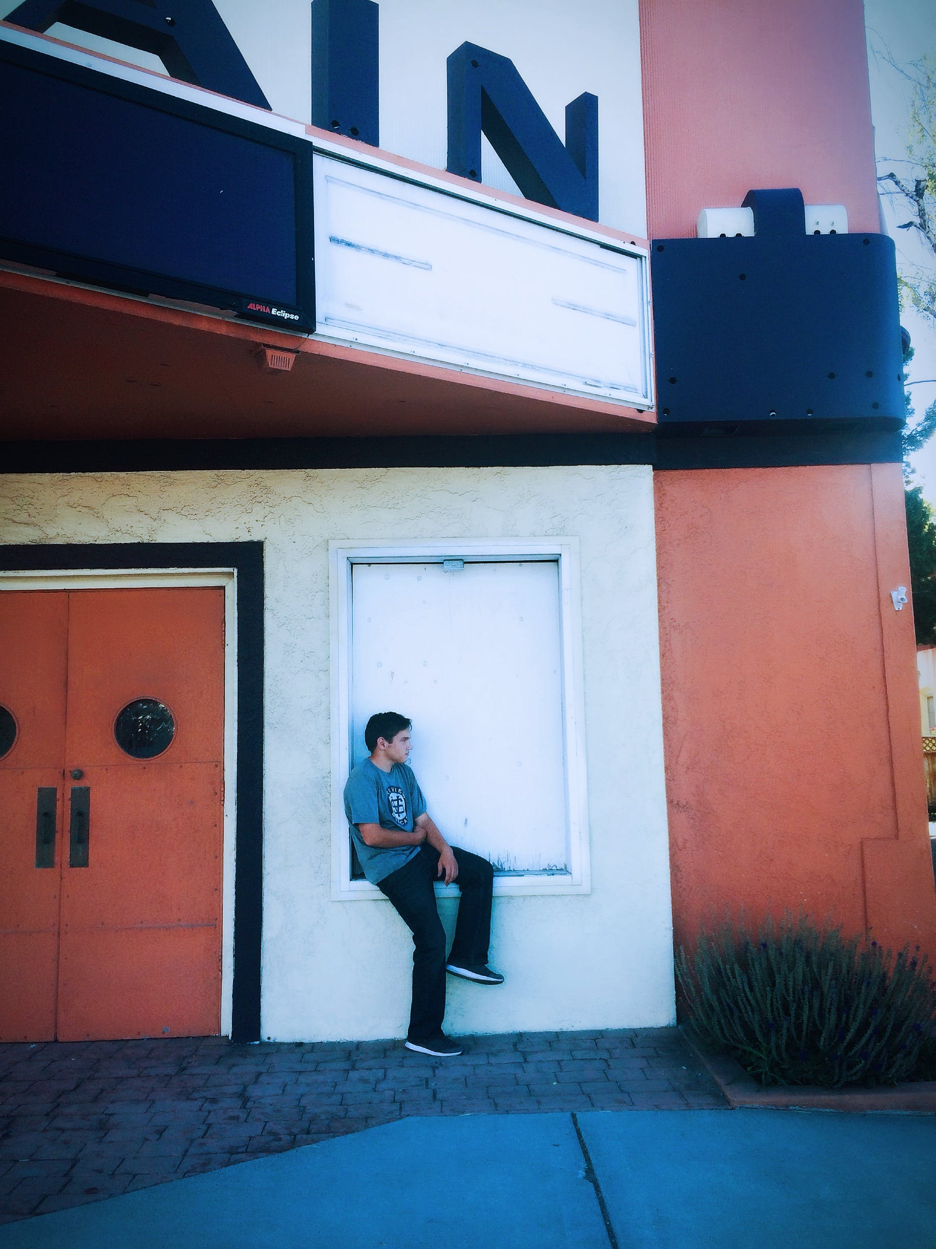 Man Sitting On A Closed Window Of A Building