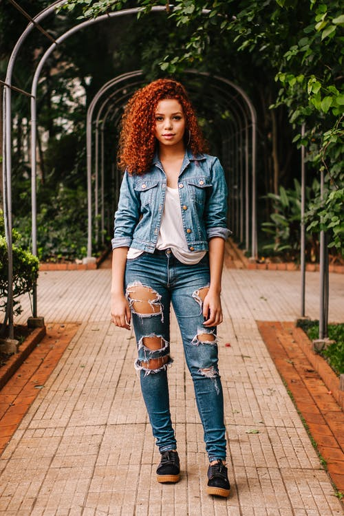 Woman In White Shirt, Blue Denim Jacket And Blue Distressed Denim Jeans Standing On Pathway