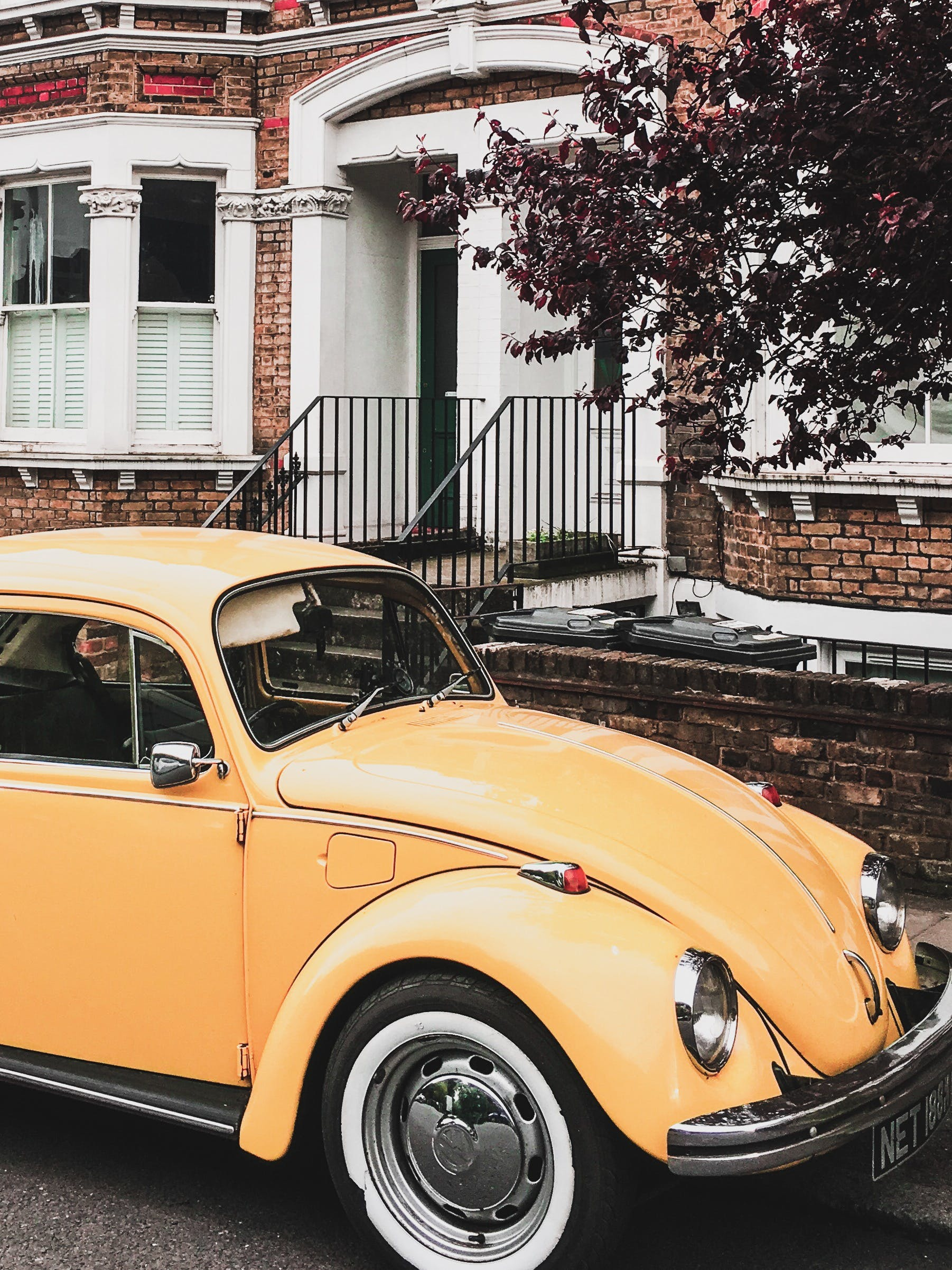 Photo of Yellow VW Beetle Parked by the Curb Next to a House