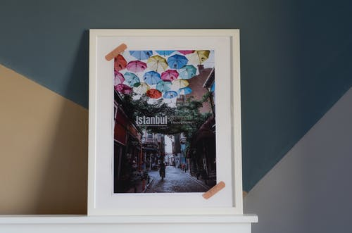 White Wooden Framed Picture of Assorted Color Umbrellas