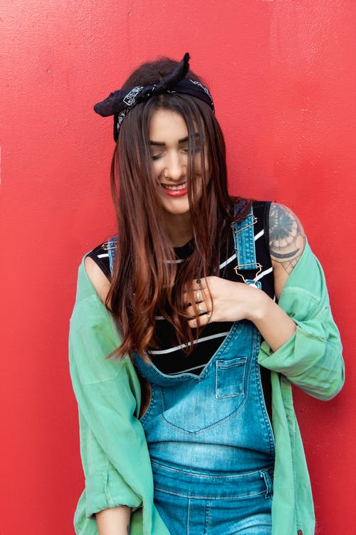 Woman in denim Dungaree Jumpsuits and Teal Jacket in Front of Red Wall