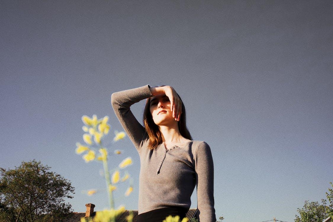 Woman in Grey Henley Long-sleeved Shirt Near Yellow Flower