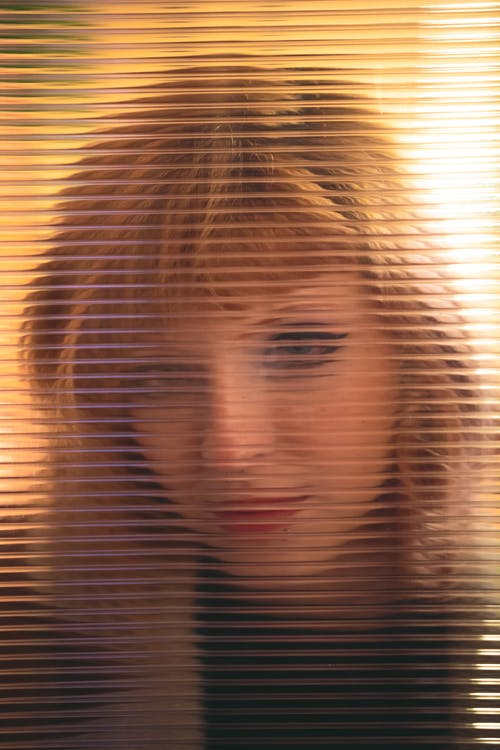 Woman in Black Shirt Behind Glass Window With Blinds