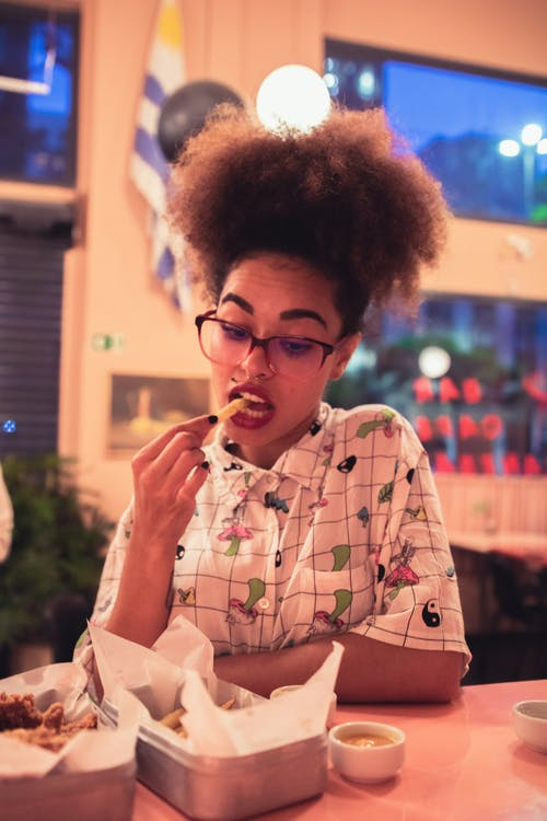 Woman in White and Green Shirt Eating Fries