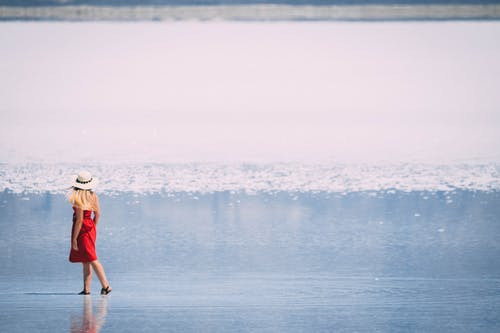 Woman in Red Tube Dress and White Hat Walking in Beach