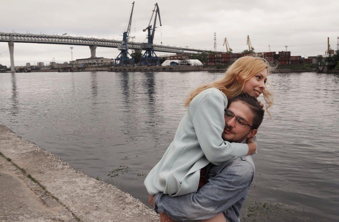 Мужчина стоит возле водоема, поднимая женщину