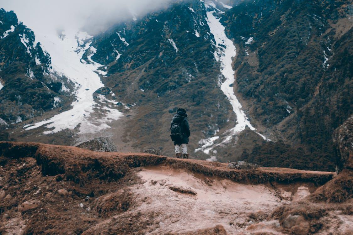 Man Standing on Ridge of Hill