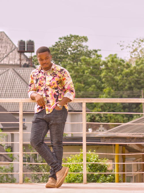 A man wearing a floral shirt and jeans leaning on a fence
