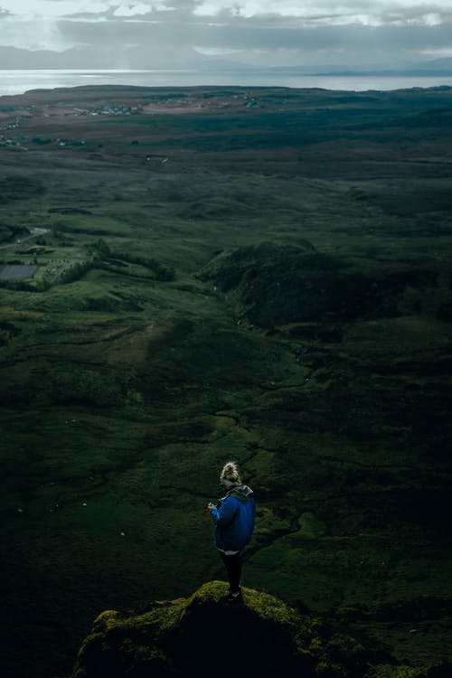 Aerial Photo of Person Standing on Edge of a Cliff