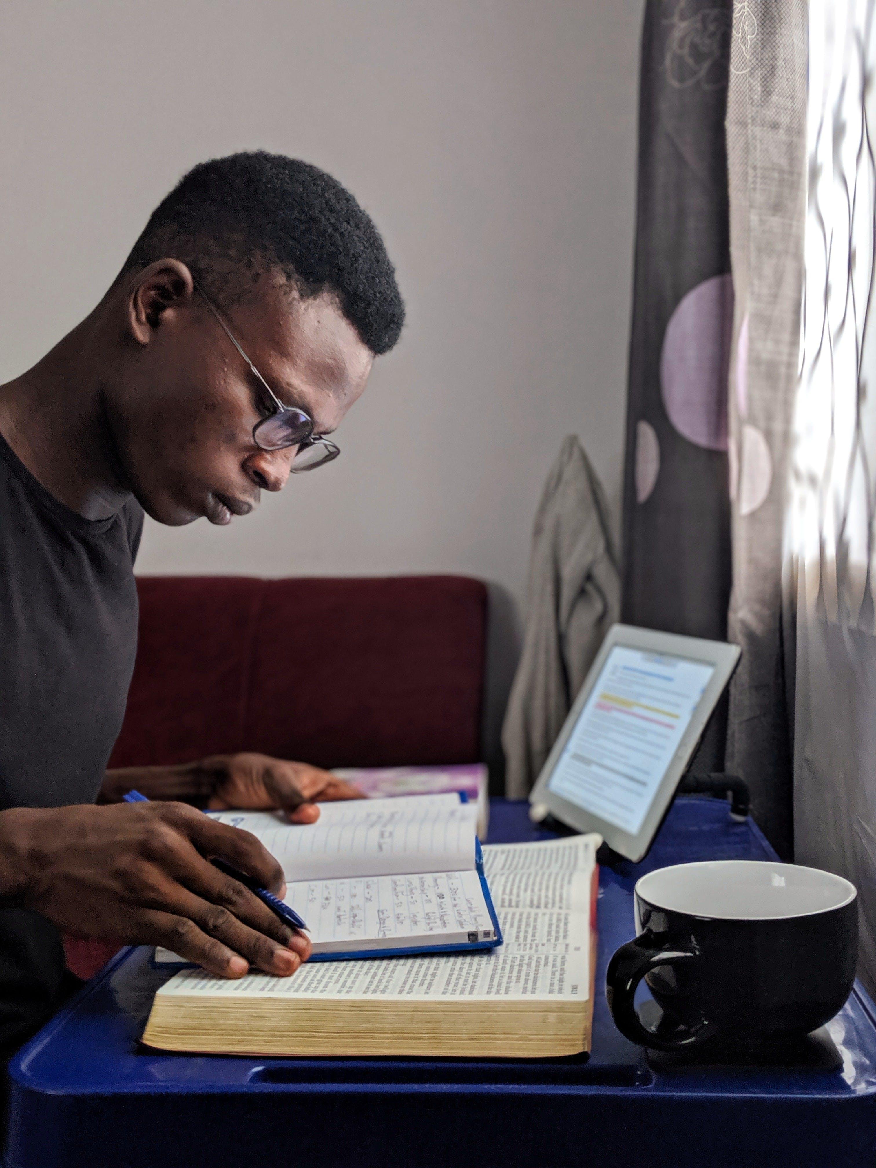 Foto d'estoc gratuïta de adult, africà, assegut, bíblia