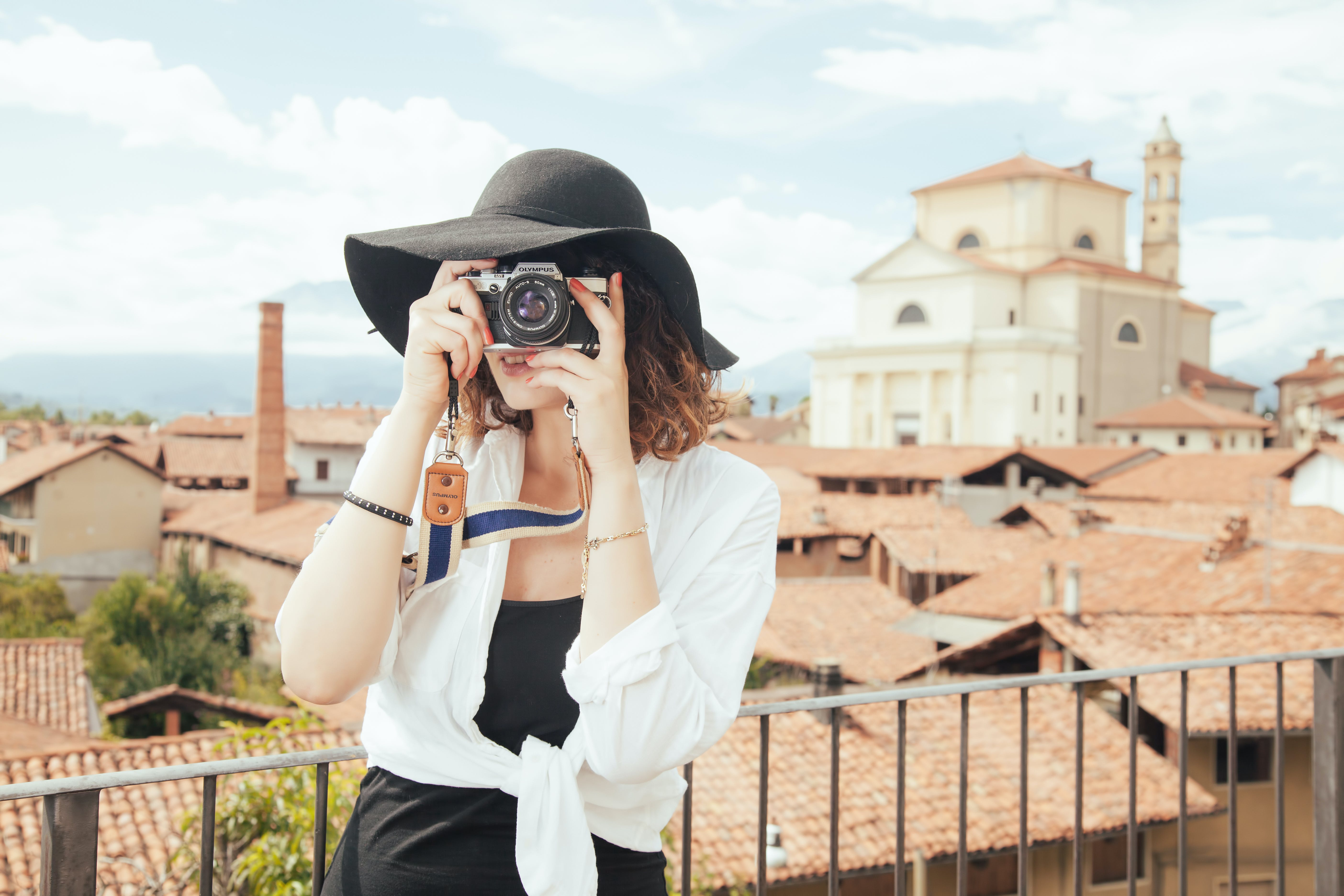 Standing Woman Taking Photo Beside Rail Next to Brown Buildings in Close-up Photography
