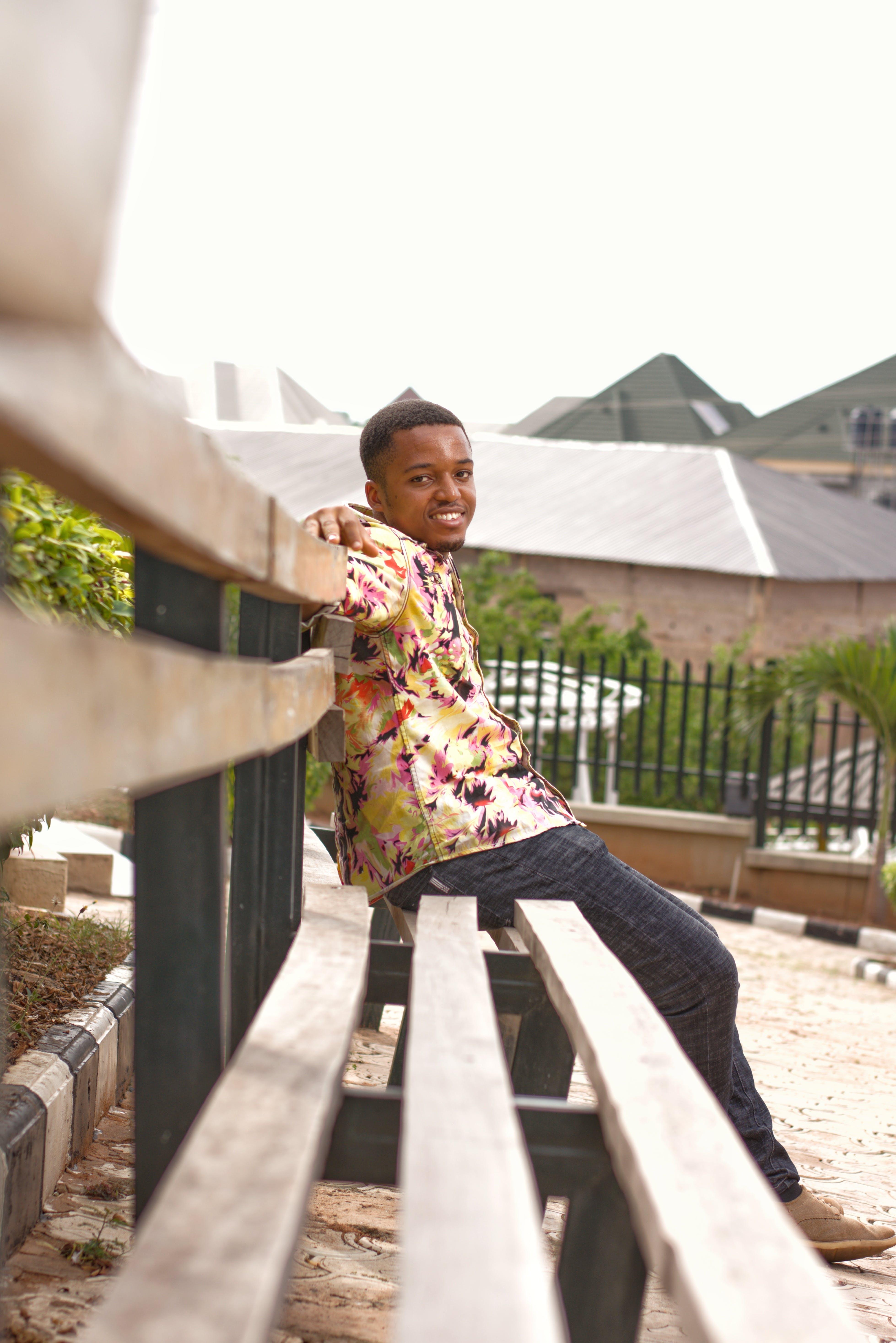 Безкоштовне стокове фото на тему «Африканський чоловік, вираз обличчя, дерев'яна лавка, людина»