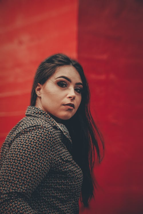 Side View Portrait Photo of Woman Posing Next To Red Building Wall