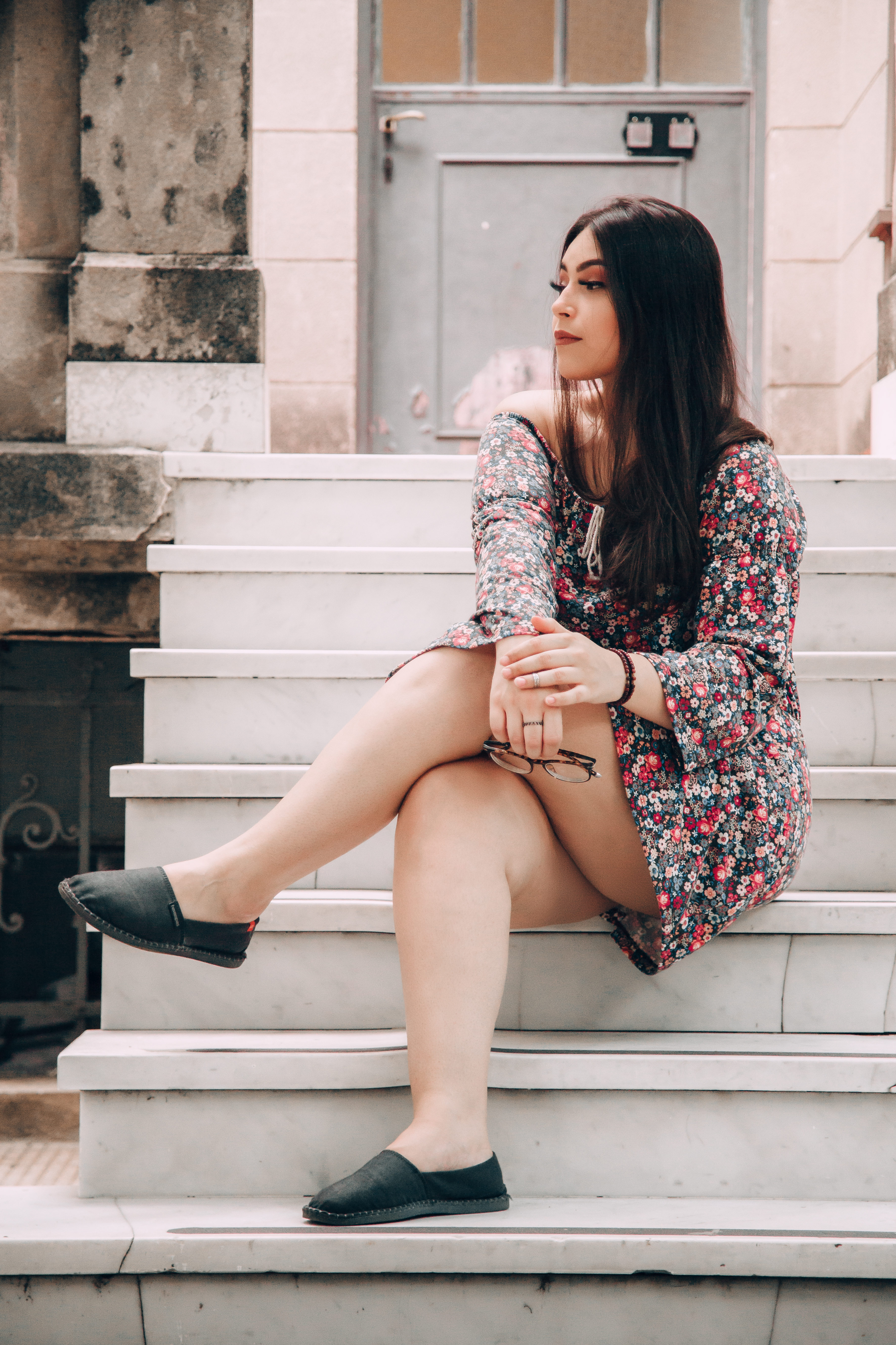 Beautiful woman in a floral dress on white stairs