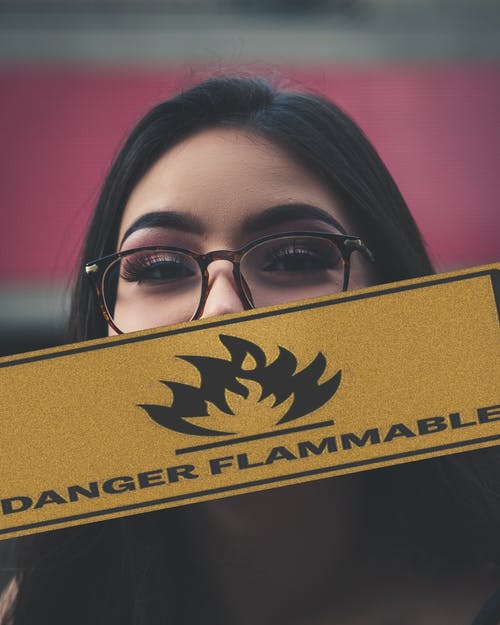 Woman Holding Danger Flammable Sign
