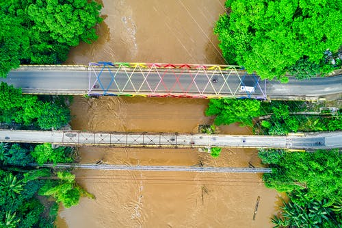 Aerial Photo of Bridge over River With Murky Flood Water