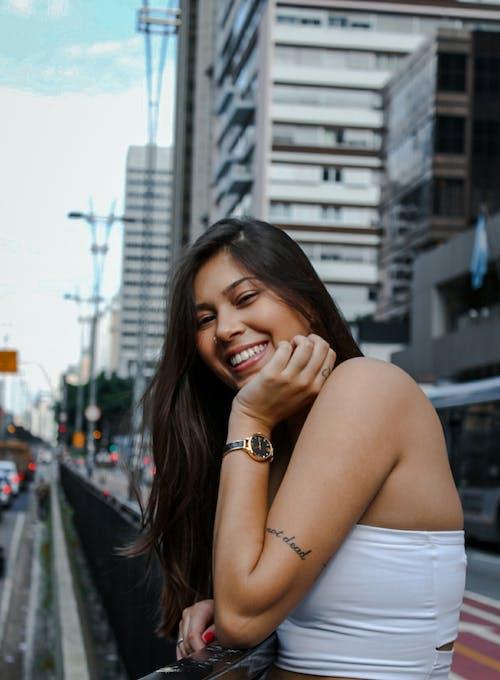 Beautiful woman wearing a white top near buildings