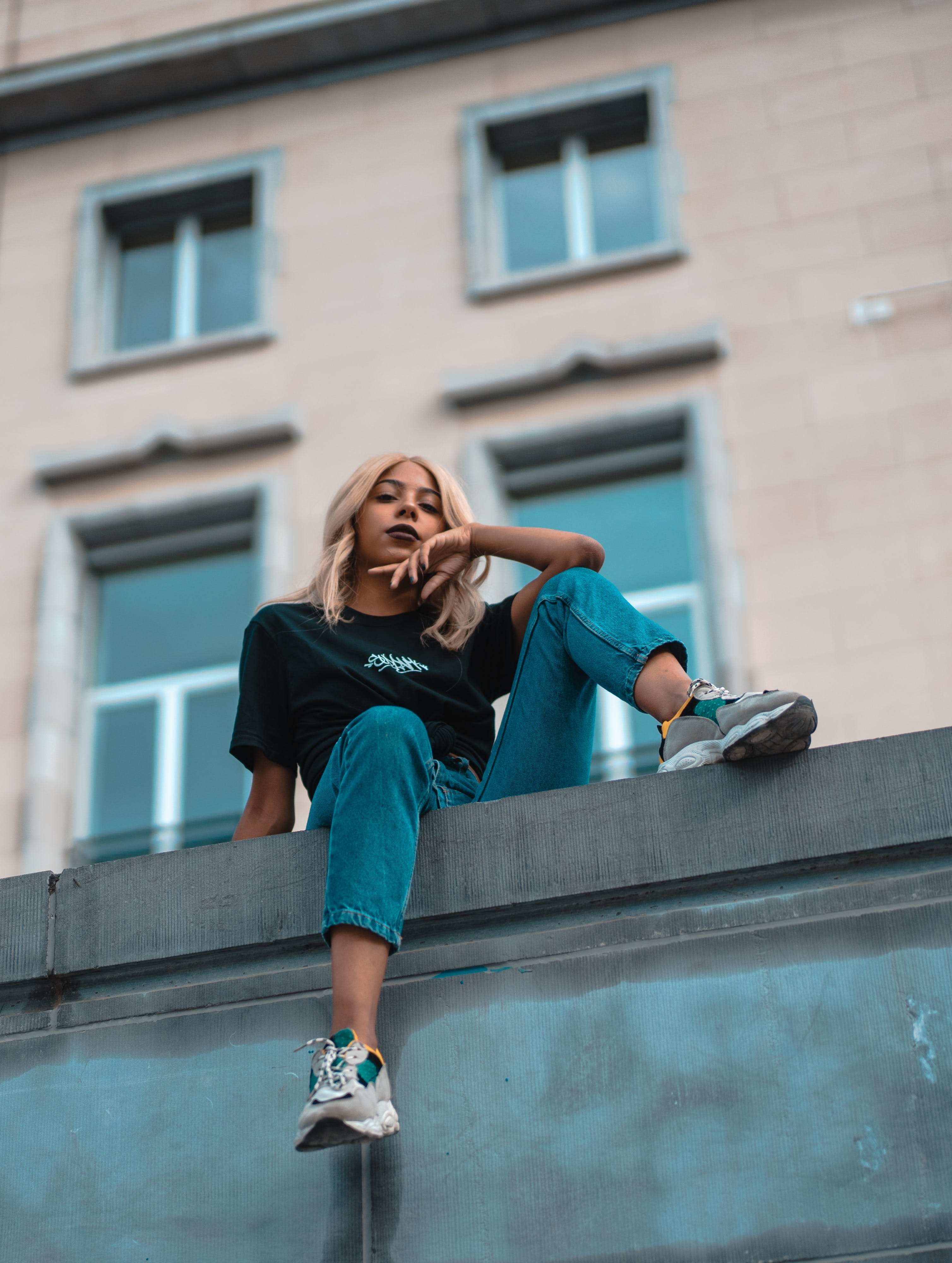 Woman With Blond Hair Sits on Top of the Building