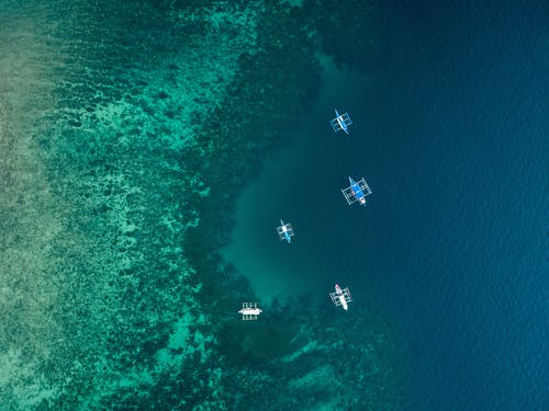 Aerial Shot of Five Boats on the Ocean
