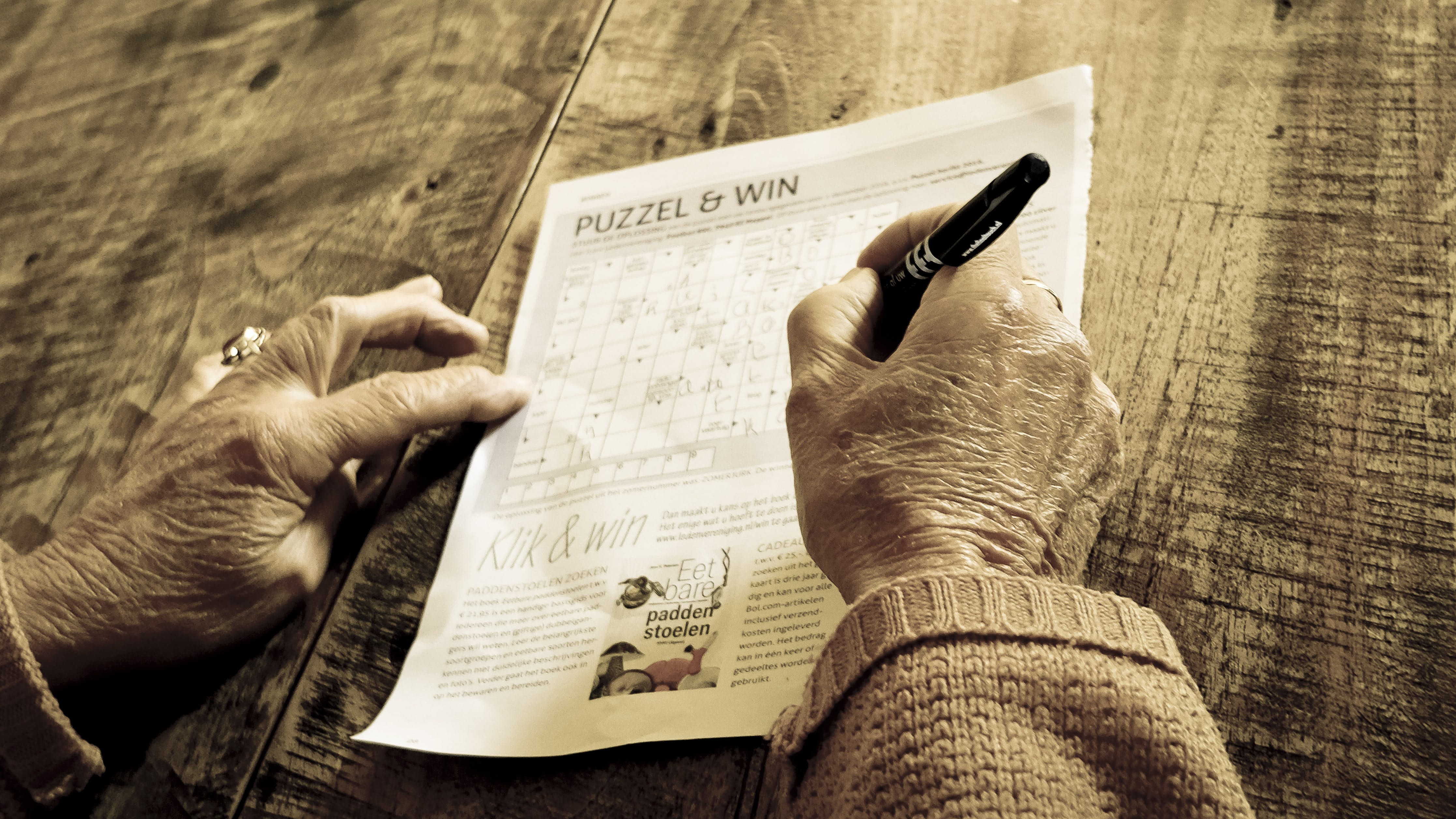 Person Writing on Puzzle & Win Paper
