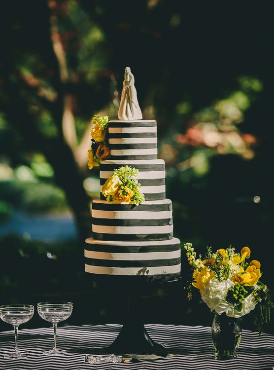 4-tier Cake next to glassware and a flower vase
