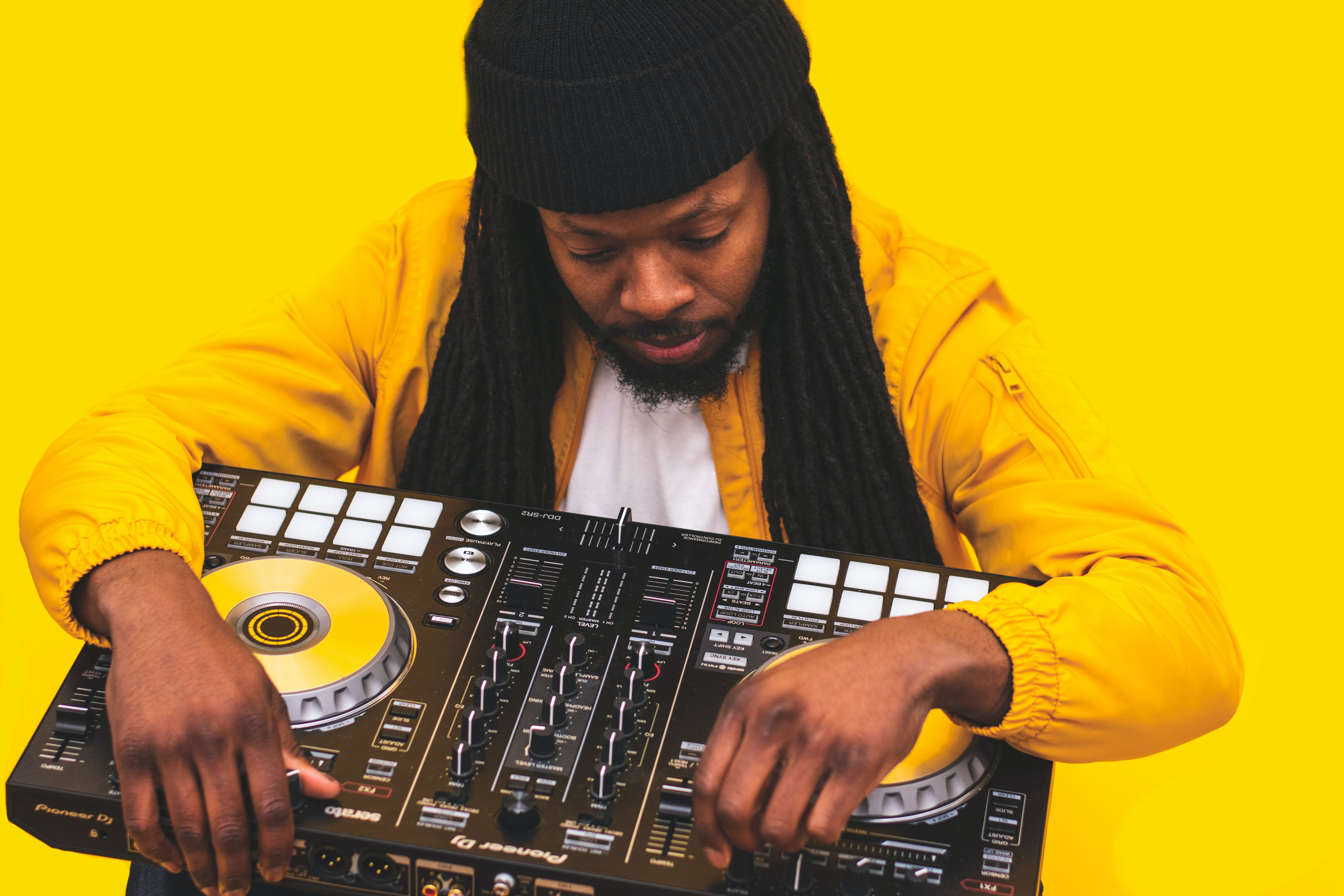 Man Holding Dj Controller on Yellow Background