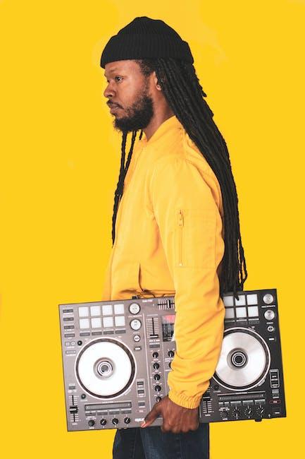 Man wearing yellow jacket holding black dj turntable