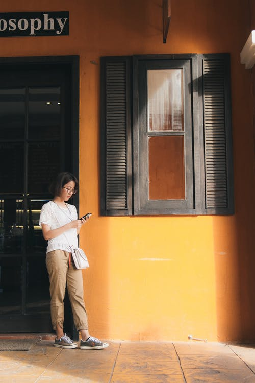 Woman Standing Near Wall Using Phone