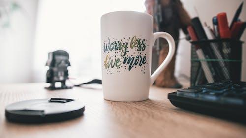 Kostenloses Stock Foto zu arbeitsplatz, becher, motivation, schreibtisch