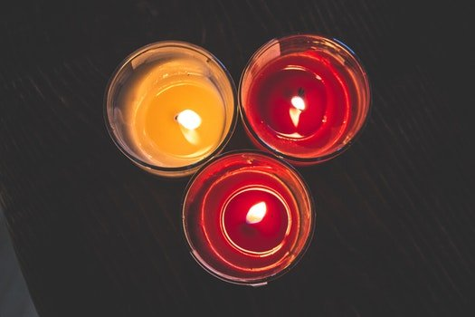 Lighted Red Wax Candle on Clear Drinking Glass