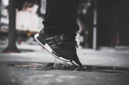 Grayscale Photo of Person Wearing Adidas Nmd Jumping on Puddle