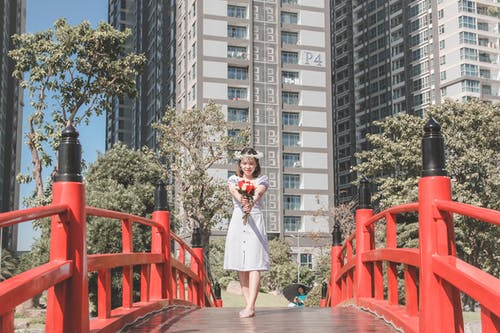 Photo of Woman in White Dress and Flower Crown Standing on Bridge While Holding Flowers