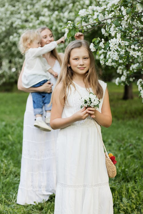 Family Picking  Flowers From A Tree