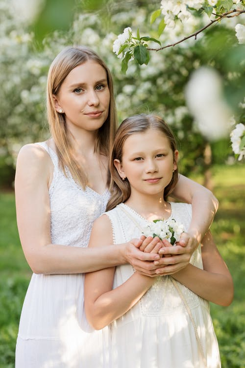 Woman and Girl Holding Flower Bouquet