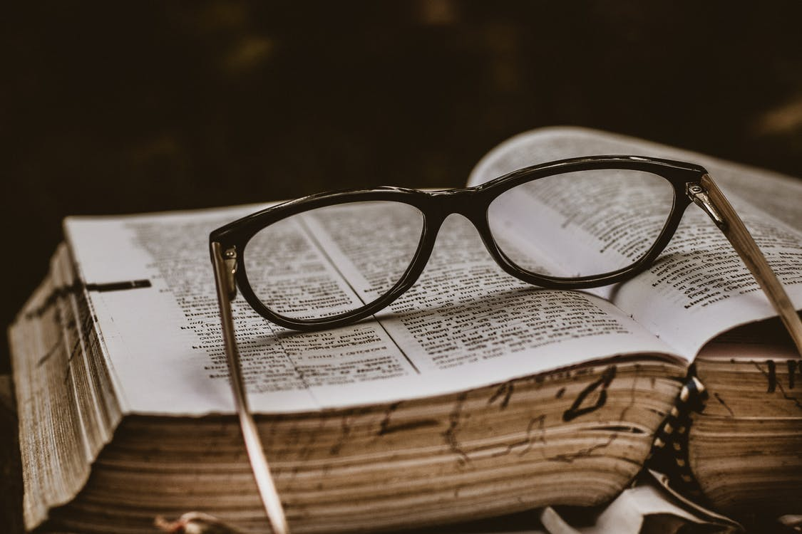 Black Framed Eyeglasses on Top of Open Book