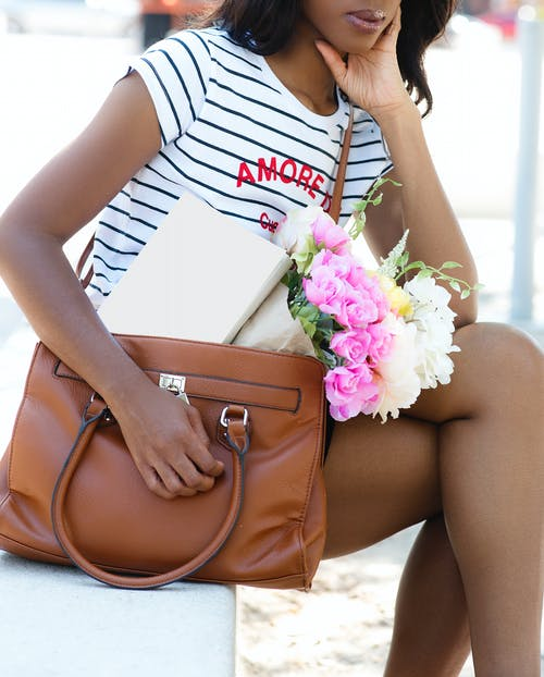 Woman Wearing White and Black Striped Shirt and Brown Leather Handbag