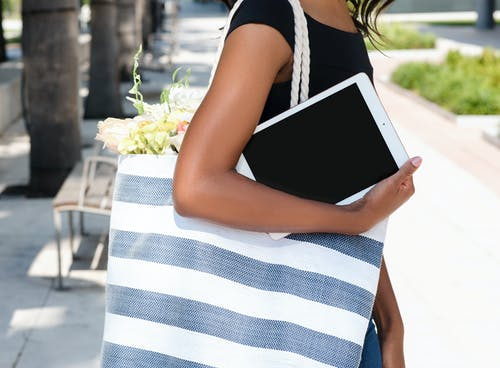Woman in Black Top Holding Ipad and Carrying White and Gray Striped Bag